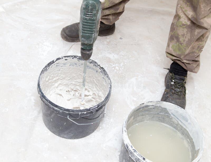 Работник смешивает решение с белым гипсолитом стоковые фото