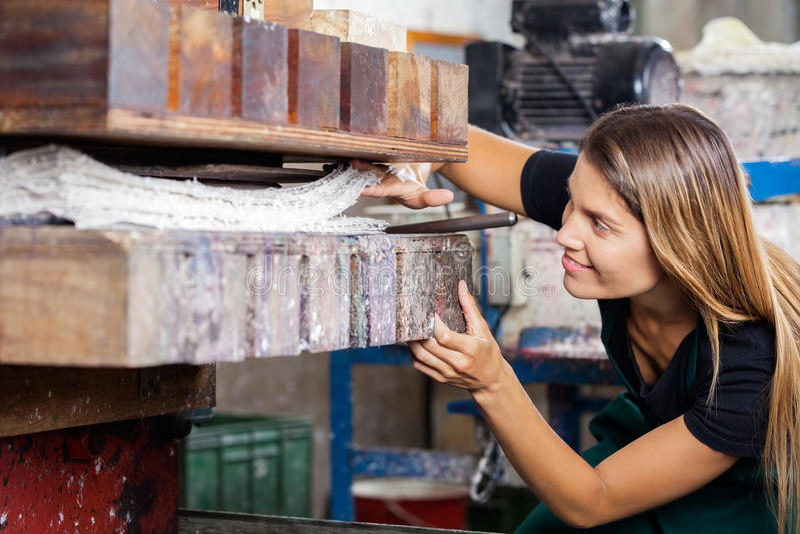 Работник смотря бумаги в машине прессы стоковые изображения rf
