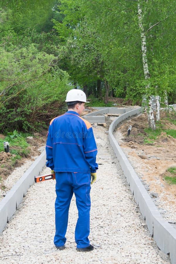 Работник стоит и держит в его руках уровень для того чтобы измерить наклон дороги которая строится стоковые изображения