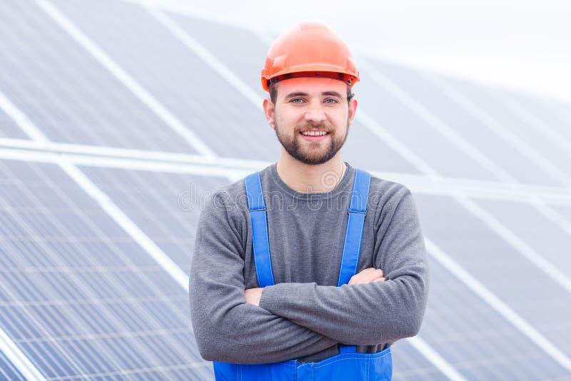 Работник стоит при его оружия пересеченные на фоне панелей солнечных батарей стоковые изображения rf