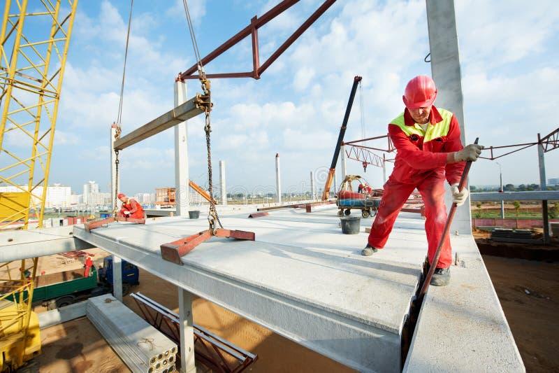 Работник строителя устанавливая бетонную плиту