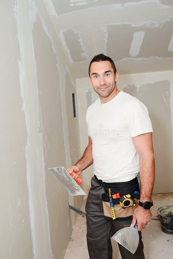 Работник строительной промышленности с инструментами штукатуря стены и восстанавливая дом в строительной площадке стоковая фотография rf