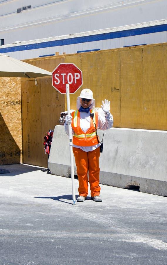 Работник строительства дорог показывает Стоп-знак стоковая фотография