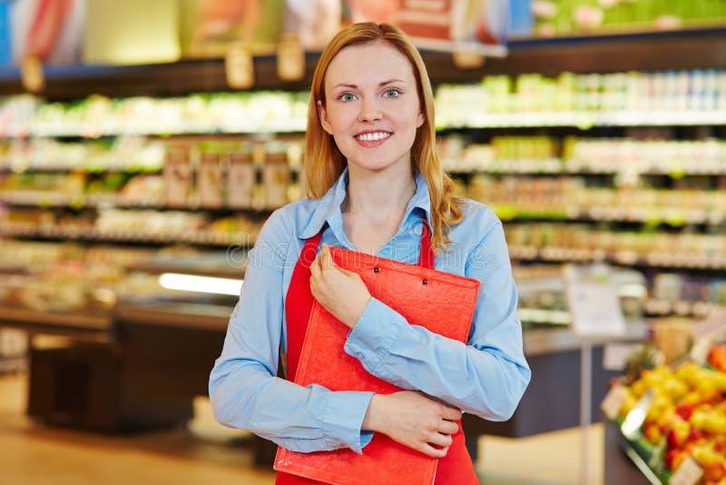 Работник супермаркета с доской сзажимом для бумаги стоковая фотография