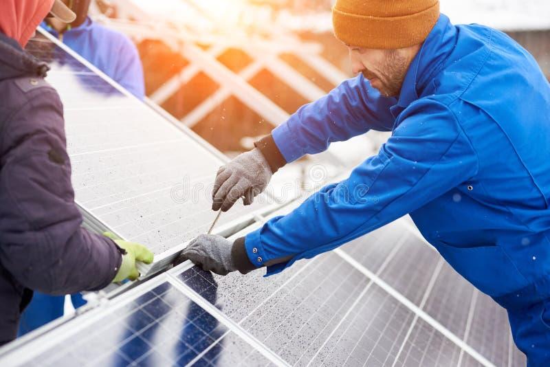 Работник с инструментами поддерживая фотовольтайческие панели Инженеры устанавливая панели солнечных батарей стоковое фото