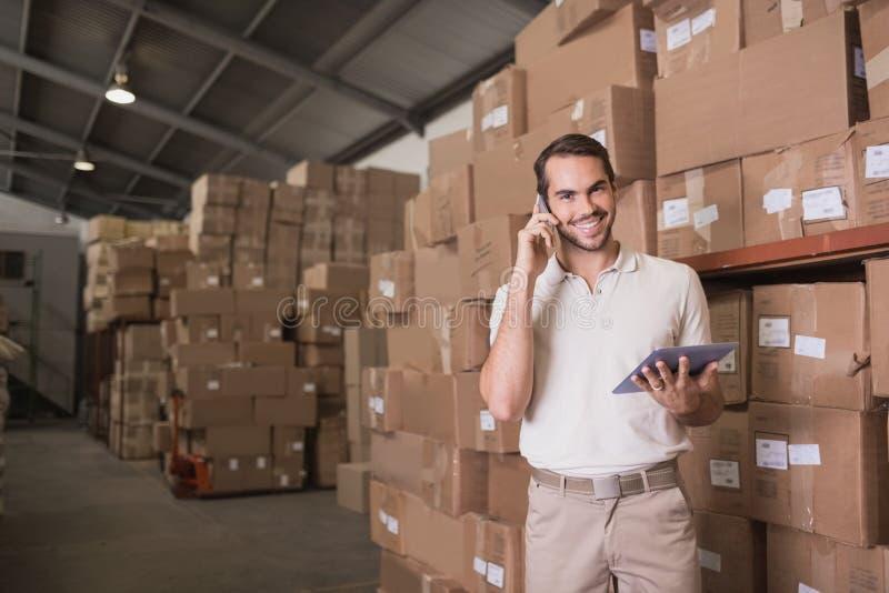 Работник с мобильным телефоном и цифровой таблеткой в складе стоковое изображение rf