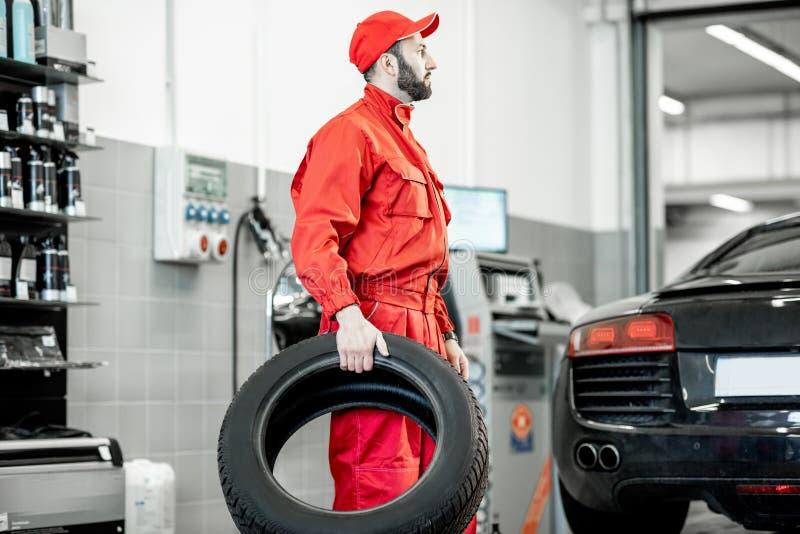 Работник с новыми автошинами на магазине или обслуживании стоковые фото