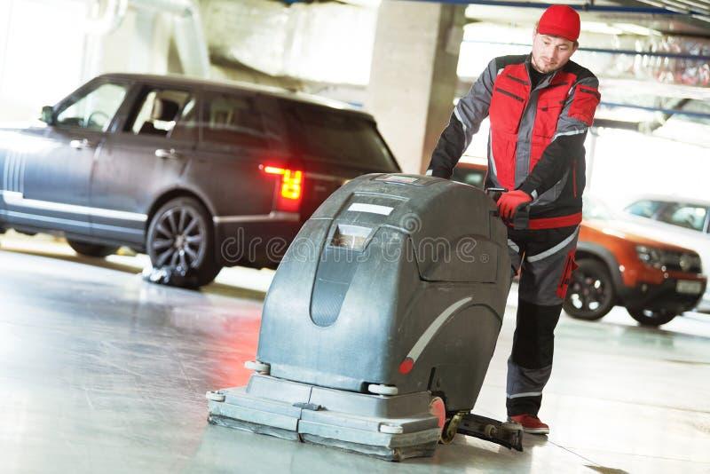 Работник с полом чистки машины в гараже стоковые фото