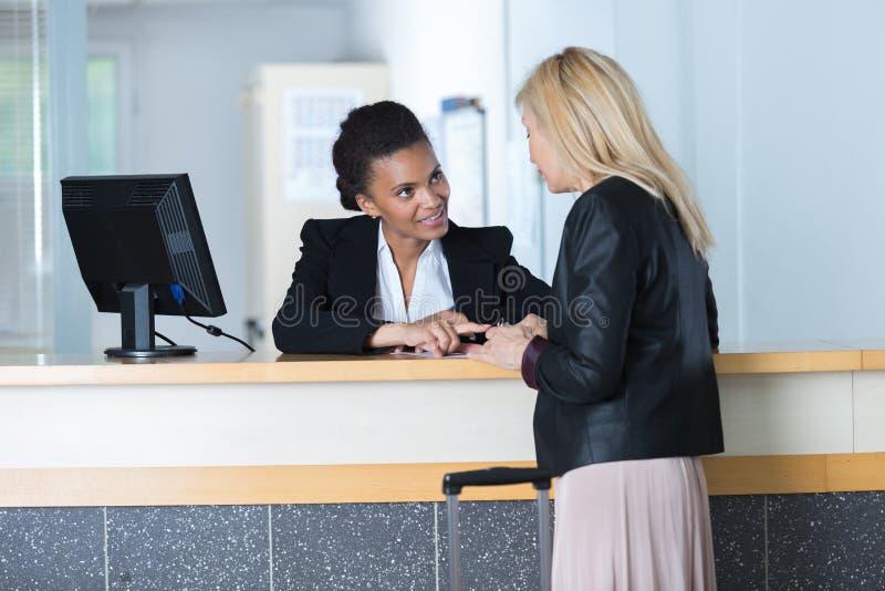 Работник службы рисепшн гостиницы делая регистрацию для клиента стоковое изображение rf