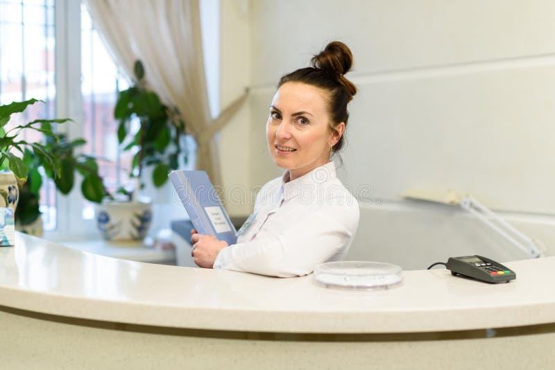 Работник службы рисепшн женщины в медицинском пальто стоит на приемной стоковые фото