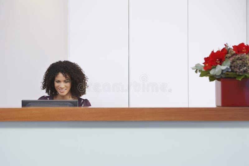 Работник службы рисепшн используя компьютер на приемной стоковое фото
