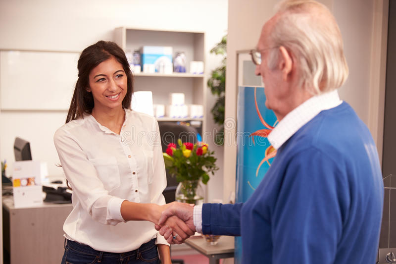Работник службы рисепшн приветствуя старшего мужского пациента на клинике слуха стоковые фотографии rf