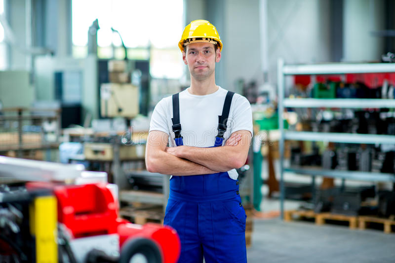 Работник с шлемом в фабрике стоковые изображения rf