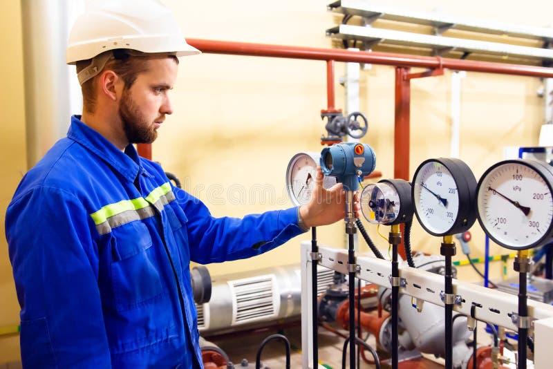 Работник техника на проверках рафинадного завода нефти и газ давит манометры стоковая фотография rf