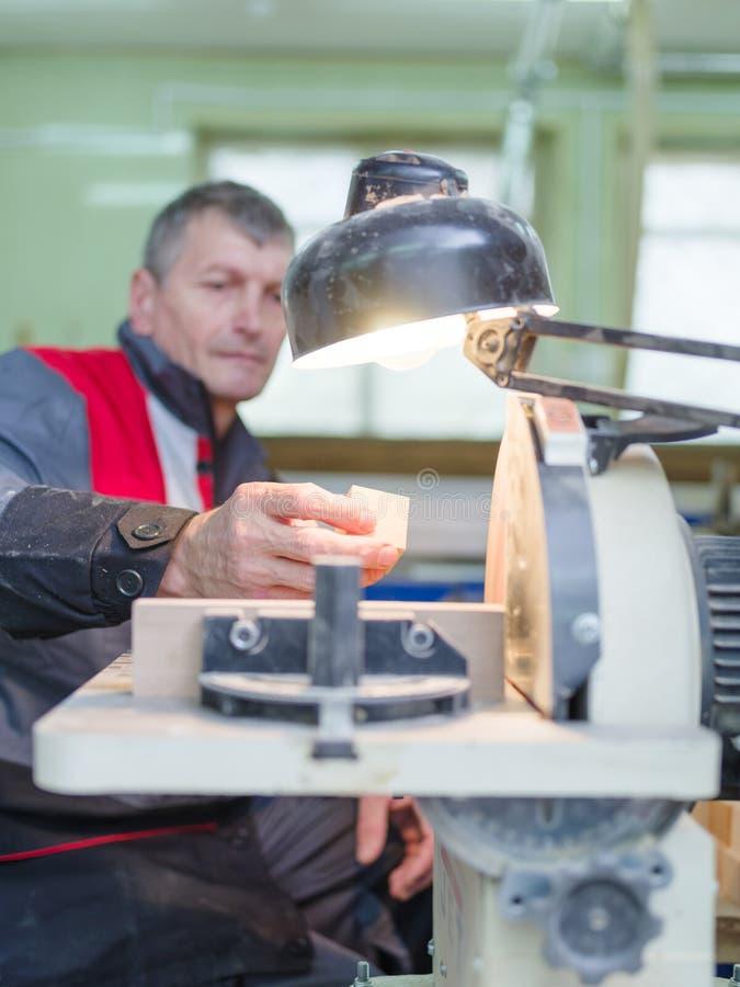 Работник точит часть под светом ` s лампы стоковая фотография