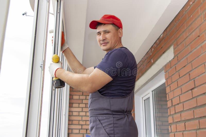 Работник устанавливает рамку sverdit окна мастерскую для того чтобы прикрепиться для того чтобы основать ремонт в многоэтажном зд стоковая фотография rf