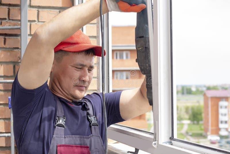 Работник устанавливает рамку sverdit окна мастерскую для того чтобы прикрепиться для того чтобы основать ремонт в многоэтажном зд стоковые изображения
