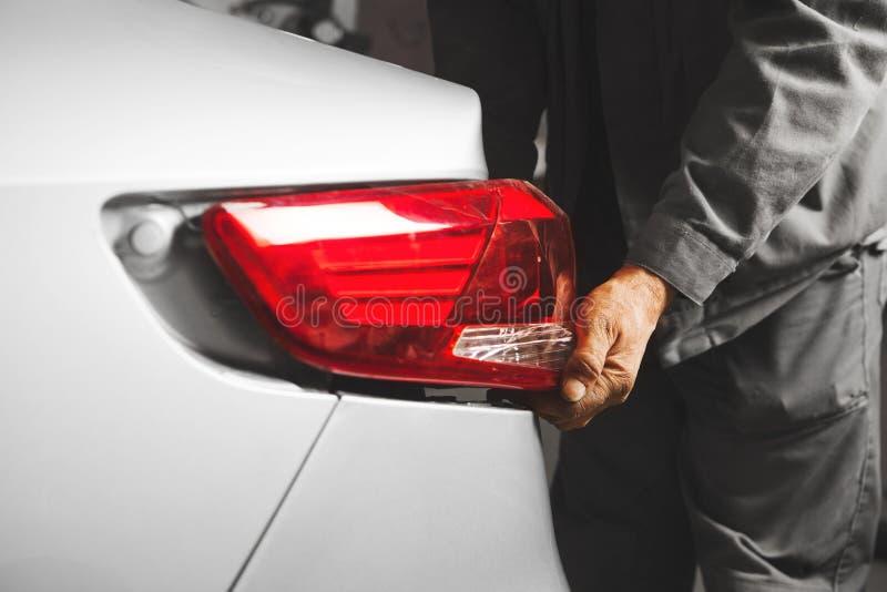 Работник устанавливает свет кабеля на автомобиле Замените задней лампы к кораблю стоковые изображения rf