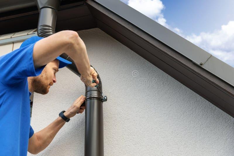 Работник устанавливая сточную канаву крыши дома стоковое изображение rf