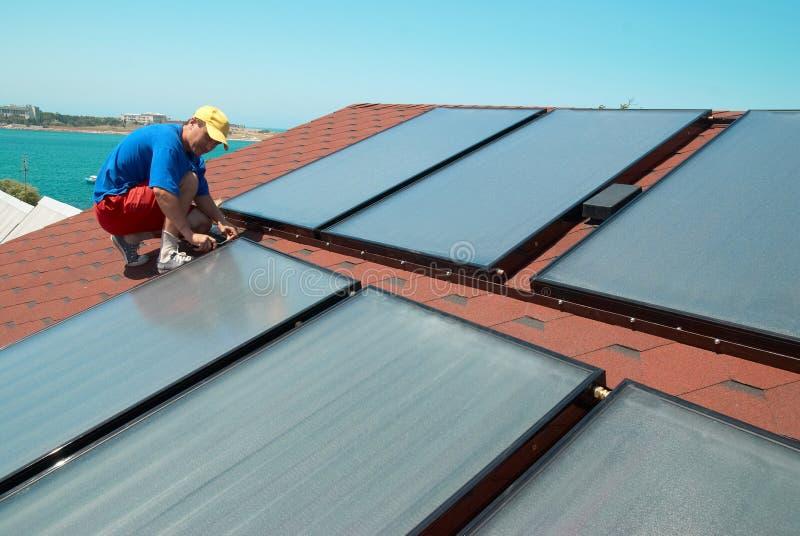 Работник устанавливает панели солнечных батарей стоковое изображение