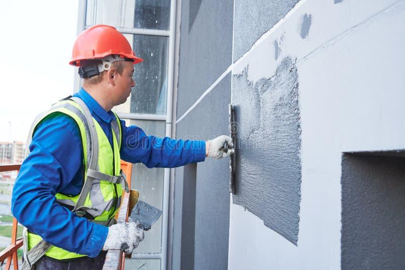 Работник фасада штукатуря внешняя стена здания стоковая фотография rf