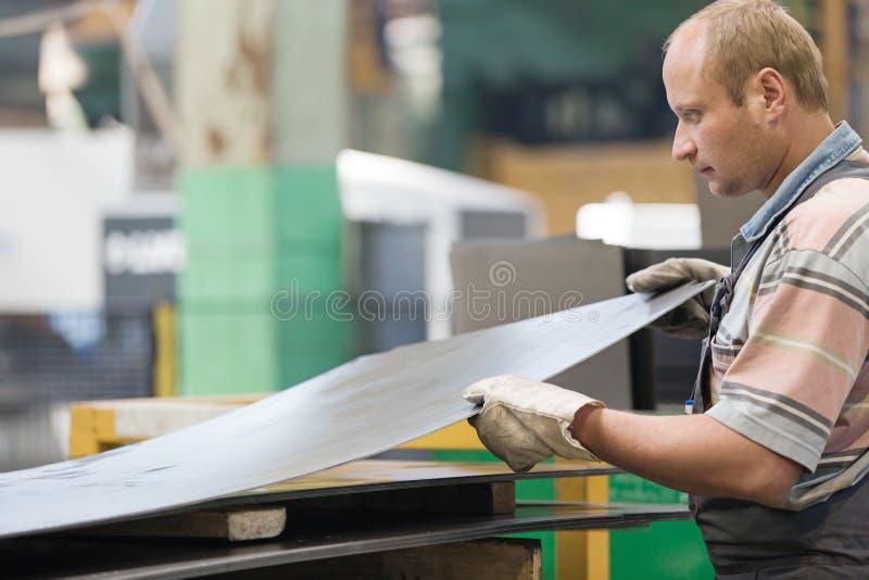 Работник человека фабрики держа металлический лист в мастерской стоковая фотография rf