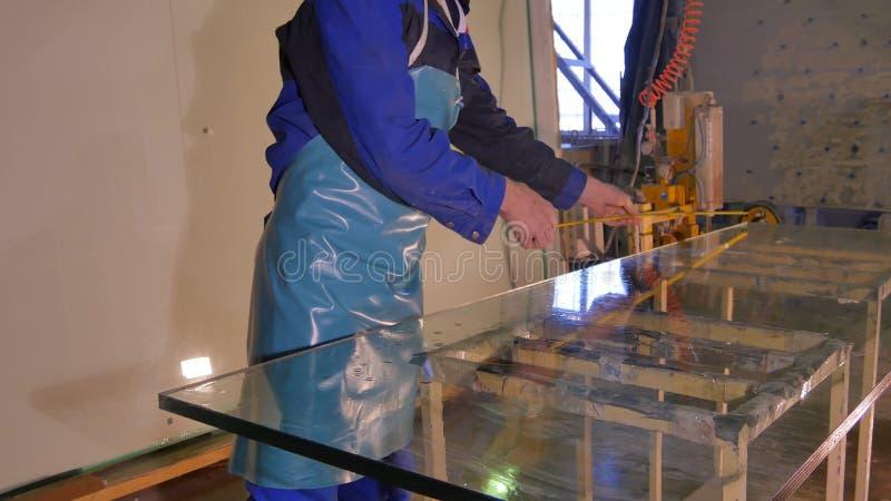 Работник чистый и сушит стекло на изготовлении Усмехаясь средняя взрослая чистка работника мылит юг на стеклянном окне с скребком стоковые фото