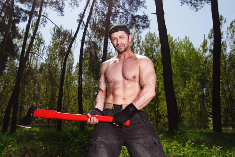 Работник Lumberjack стоя в лесе с осью стоковое фото