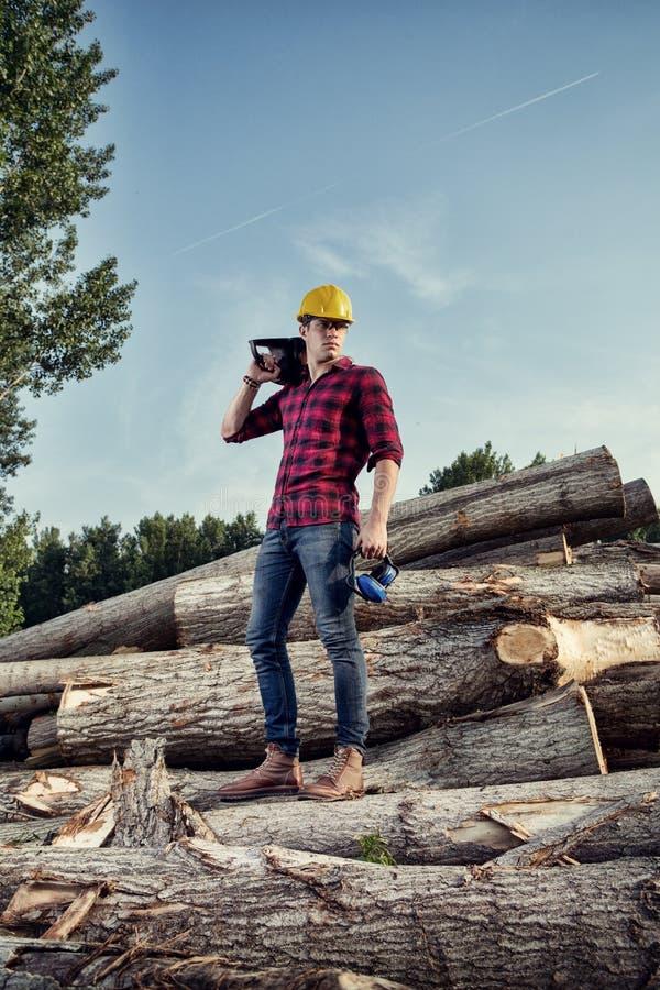 Работник Lumberjack стоя в лесе стоковые фотографии rf