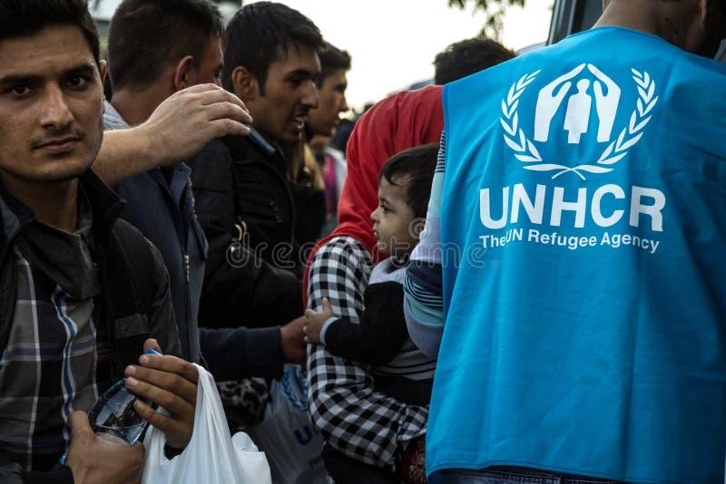 Работник UNHCR, агенства Организации Объединенных Наций для беженцев, стоя перед толпой беженцев, включая младенца стоковая фотография rf
