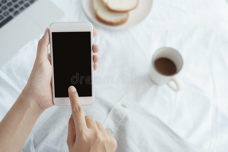 Работница рук держа и используя умный телефон на предпосылке стола На столе имейте кофе, хлебы и ноутбук чашки стоковые фотографии rf