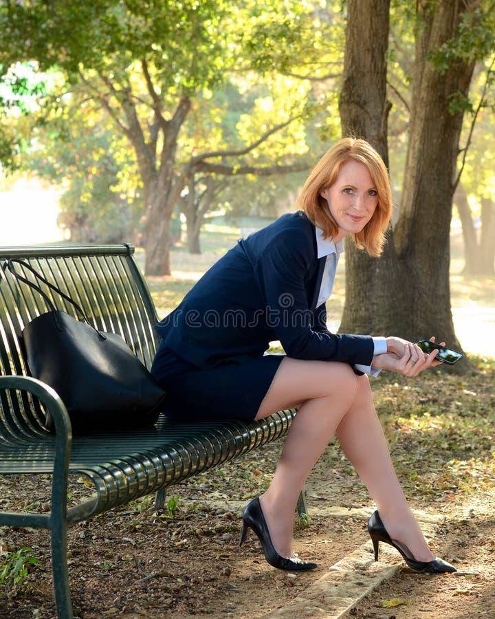 Работница с телефоном на скамейке в парке стоковое фото