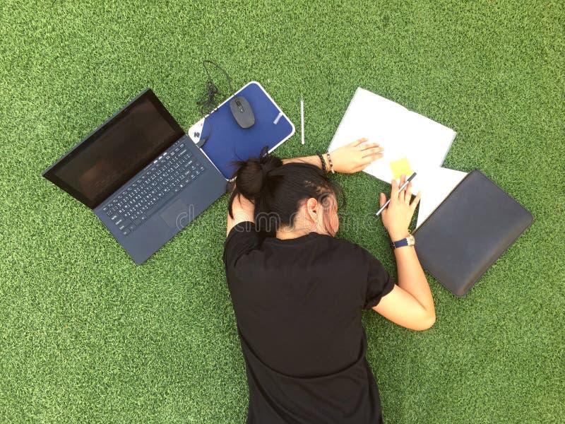 Работница усилила вне от работы и удержания головы с положением вниз на зеленой траве стоковые изображения rf