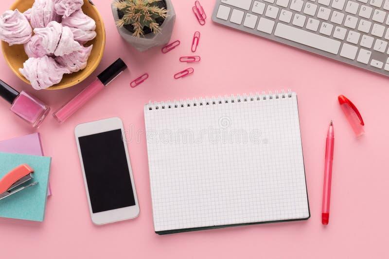 Рабочая зона с блокнотом и smartphone на розовой предпосылке стоковая фотография