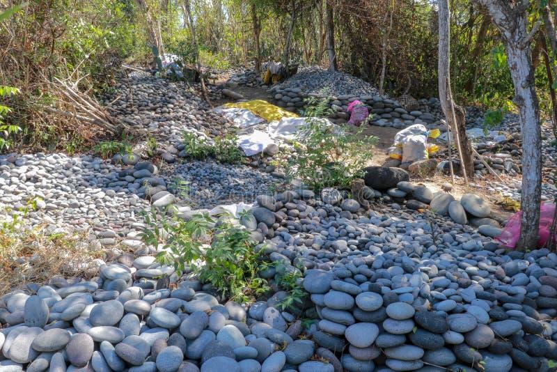 Рабочее место балийских каменных сборщиков Сортированные валуны размером Естественный строительный материал Тяжелая работа Камни  стоковые фото