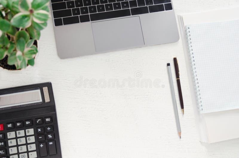 Рабочее место в офисе - столе с компьтер-книжкой, калькулятором, стогом бумаг, тетрадью, ручкой и зеленым растением стоковое изображение rf