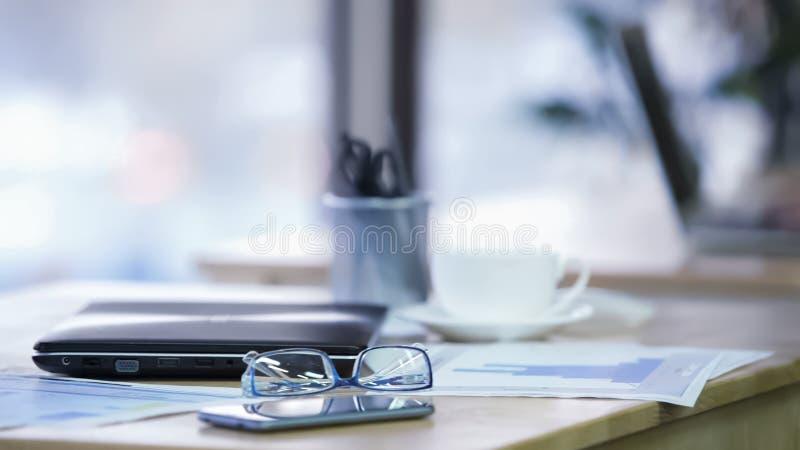 Рабочее место в офисе, eyeglasses, smartphone и закрытой компьтер-книжке лежа на таблице стоковые изображения