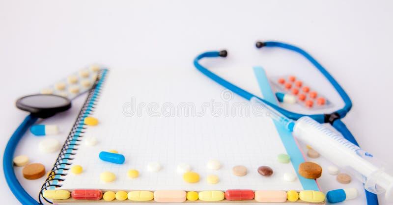 Рабочее место доктора - стетоскопа, тетради, медицинских деталей и пилюлек на столе Концепция само-лекарства, социальной медицины стоковая фотография