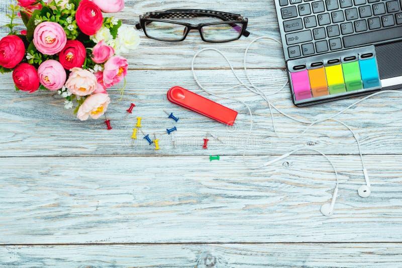 Рабочее место: компьтер-книжка, стекла и цветки стоковое изображение