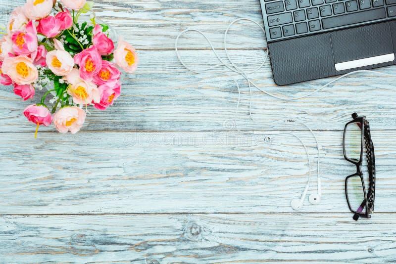 Рабочее место: компьтер-книжка, стекла и цветки стоковая фотография rf