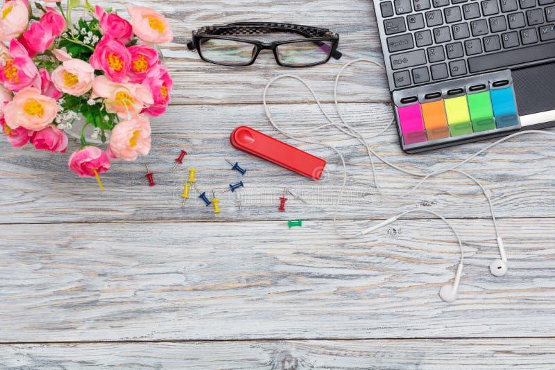 Рабочее место: компьтер-книжка, стекла и цветки стоковые фото