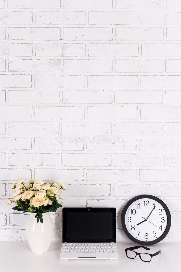 Рабочее место - компьтер-книжка с пустым экраном, часами офиса, стеклами и стоковое фото rf