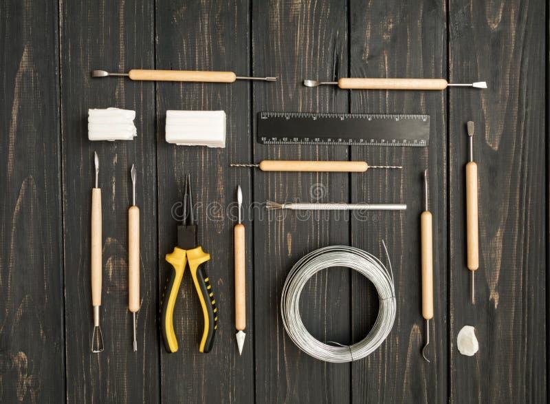 Рабочее место мастера, подготавливает для ваять от глины полимера Винтажная таблица деятельности с инструментами прессформы Плоск стоковая фотография rf