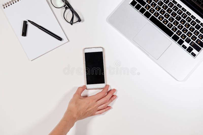 Рабочее место со смартфоном в женских руках стоковое изображение
