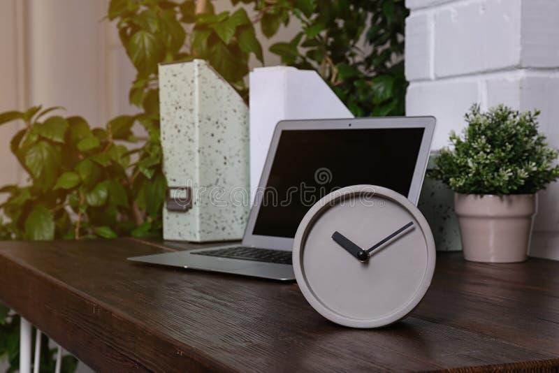 Рабочее место со стильными сетноыми-аналогов часами и ноутбуком в офисе стоковые фотографии rf