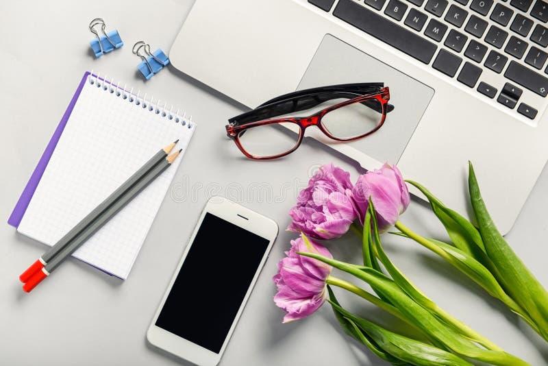 Рабочее место с канцелярскими принадлежностями, ноутбуком и телефоном на таблице r стоковые фото