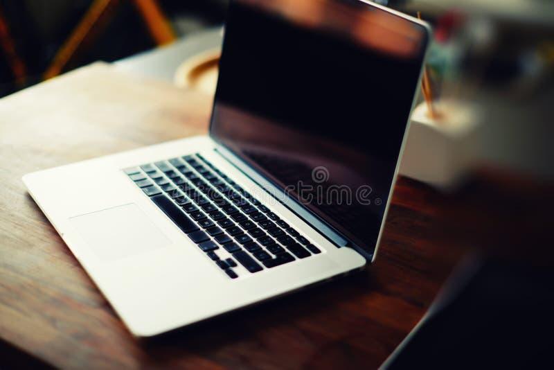 Рабочее место с открытой компьтер-книжкой с черным экраном на современном деревянном столе стоковое изображение rf