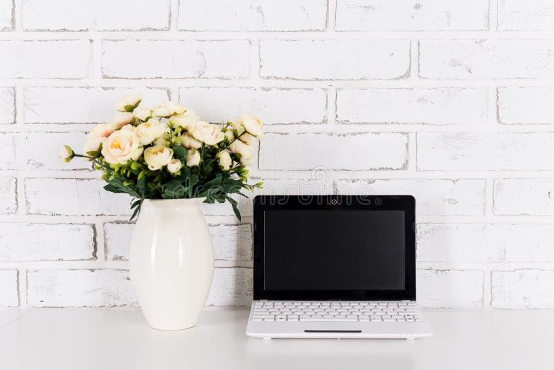Рабочее место с современной компьтер-книжкой с пустым экраном над белым кирпичом стоковые фотографии rf