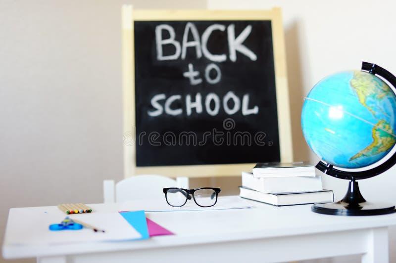 Рабочее место с столом, классн классным, глобусом и eyeglasses школы стоковое изображение