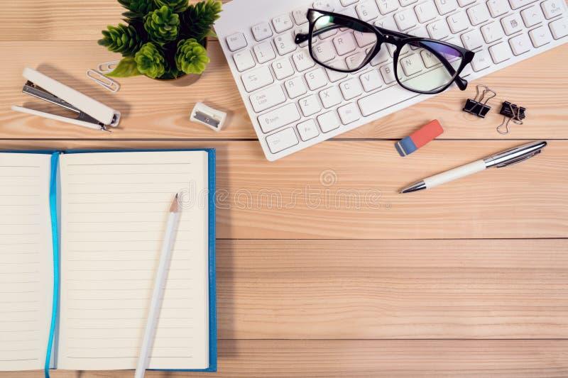 Рабочее место таблицы стола офиса с клавиатурой компьютера, стеклами, калькулятором, ручкой, карандашем и открытыми тетрадью и ƒ  стоковое фото